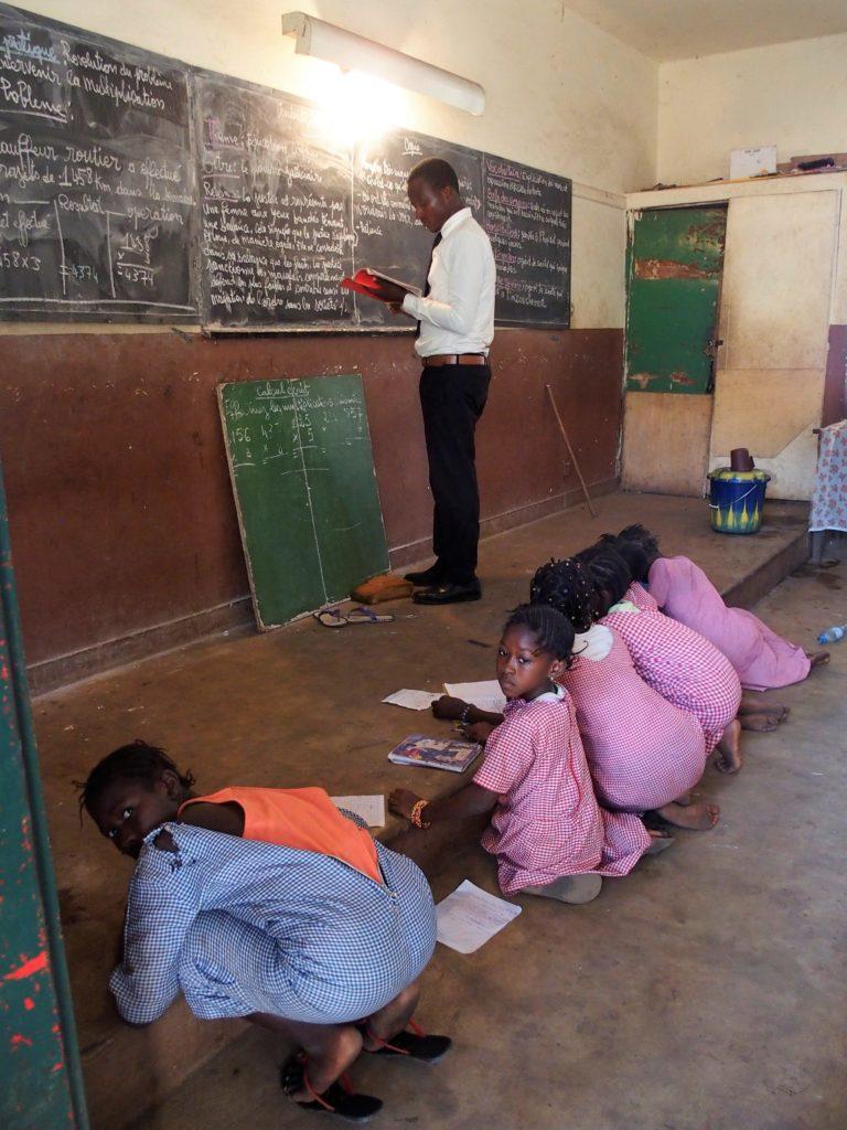 Photo 1: A l'école Tombo 2 de Conakry, des élèves, faute de place, sont contraintes de s'asseoir par terre et d'utiliser l'estrade comme table.